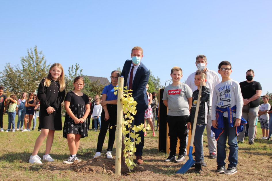 Le maire entouré d'enfants gonfrevillais prêt à planter l'arbre pour la paix.