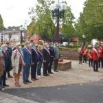 Le maire, le députe, les élus et les partenaires se tenant devant la sépulture pendant que la fanfare joue un morceau